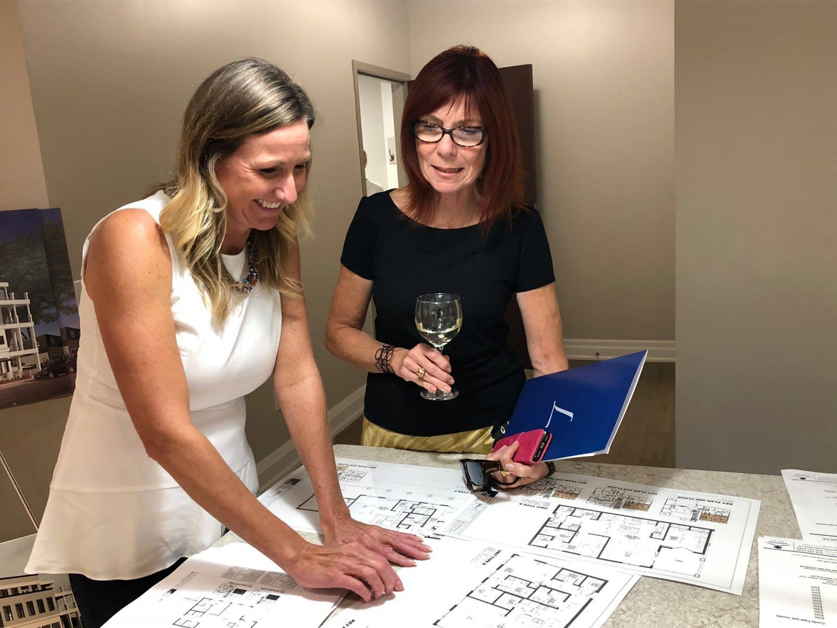 Guests reviewing floor plans at the Colonnade | Team Logue Burlington Real Estate