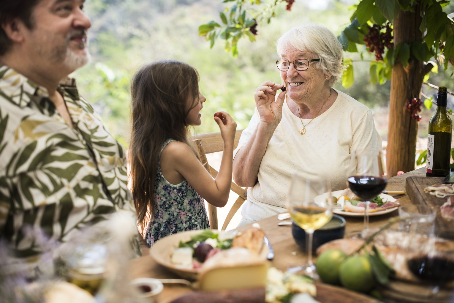 grandmother and grand daughter laughing and eating in outdoor luxury kitchen