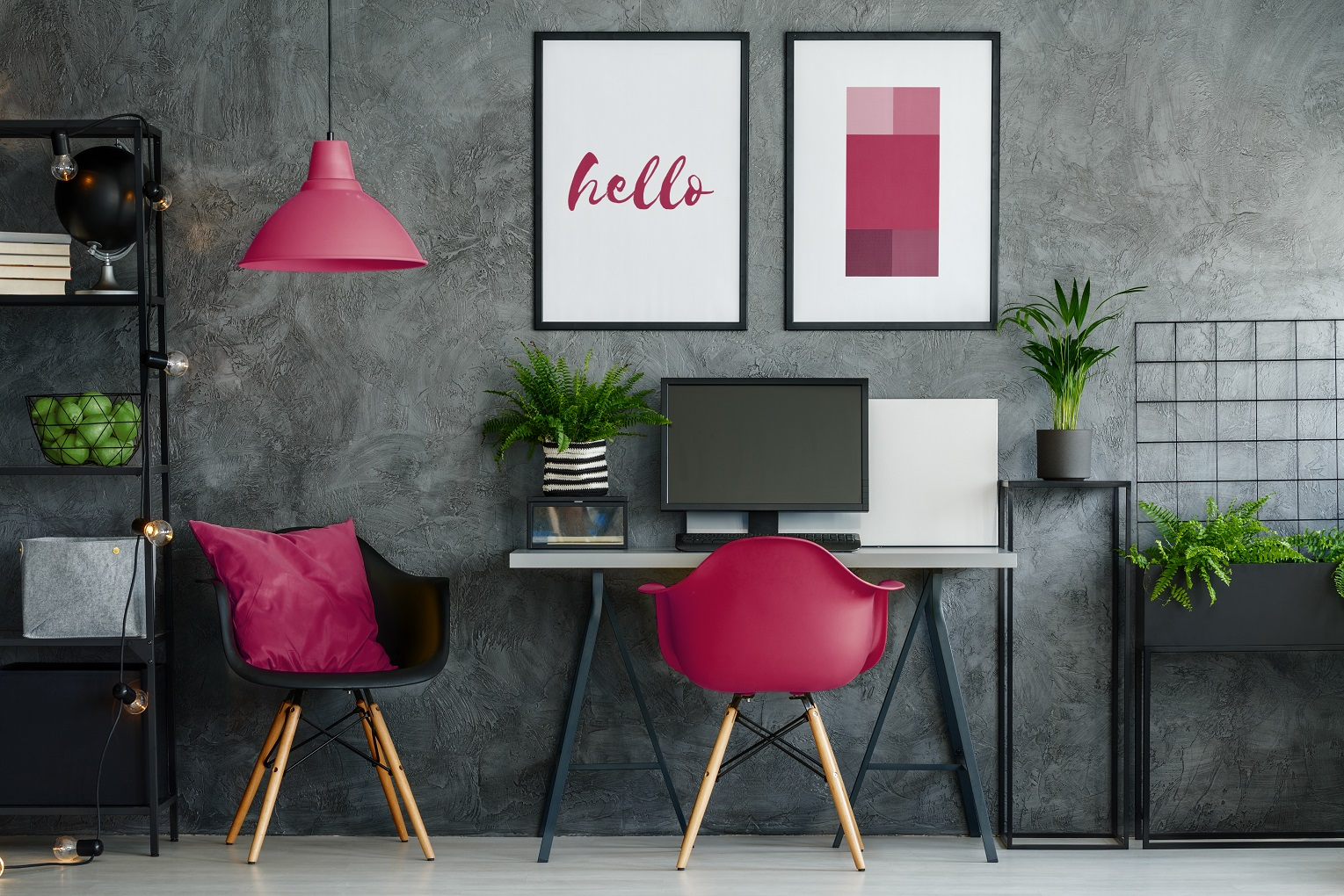 luxury home office ideas team logue Cherry pink chair at desk with desktop in dark home office with posters on concrete wall