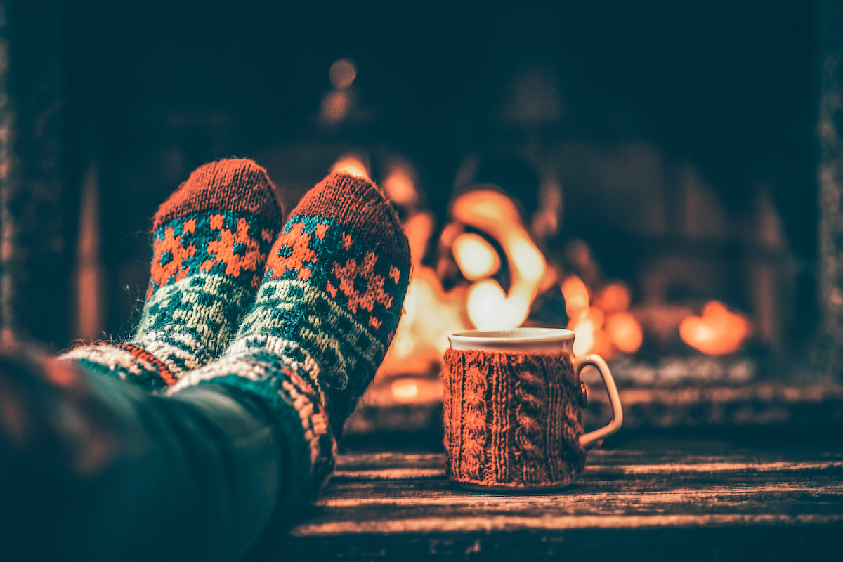 Burlington home buyers | Feet in woollen socks by the Christmas fireplace. Woman relaxes by warm fire with a cup of hot drink and warming up her feet in woollen socks. Close up on feet. Winter and Christmas holidays